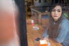 Morenita joven en café detrás de la ventana Fotos de archivo