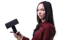 Morenita joven fruncida el ceño con el martillo grande Imagen de archivo