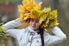 Morenita joven hermosa con una guirnalda de las hojas de otoño Fotografía de archivo libre de regalías