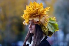 Morenita joven hermosa con una guirnalda de las hojas de otoño Imagen de archivo libre de regalías
