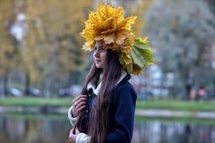 Morenita joven hermosa con una guirnalda de las hojas de otoño Foto de archivo