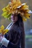 Morenita joven hermosa con una guirnalda de las hojas de otoño Fotos de archivo