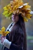 Morenita joven hermosa con una guirnalda de las hojas de otoño Fotografía de archivo