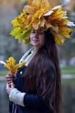 Morenita joven hermosa con una guirnalda de las hojas de otoño Fotos de archivo libres de regalías
