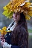 Morenita joven hermosa con una guirnalda de las hojas de otoño Foto de archivo libre de regalías