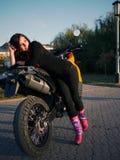 Morenita joven hermosa en el fondo de una motocicleta en th Fotos de archivo libres de regalías