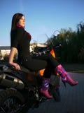 Morenita joven hermosa en el fondo de una motocicleta en th Foto de archivo