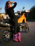 Morenita joven hermosa en el fondo de una motocicleta en th Fotos de archivo
