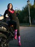 Morenita joven hermosa en el fondo de una motocicleta en th Foto de archivo libre de regalías