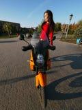Morenita joven hermosa en una motocicleta fotos de archivo