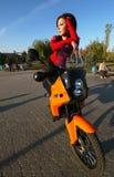 Morenita joven hermosa en una motocicleta imagenes de archivo
