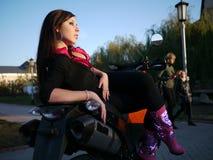 Morenita joven hermosa en una motocicleta fotografía de archivo libre de regalías