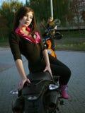 Morenita joven hermosa en una motocicleta fotos de archivo libres de regalías