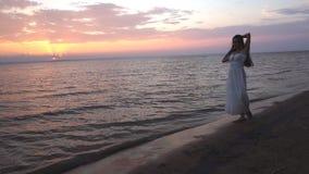 Morenita joven hermosa que camina en la playa en la puesta del sol almacen de metraje de vídeo