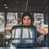 Morenita joven hermosa que presenta al lado de un vintage TV Imagenes de archivo
