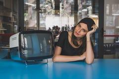 Morenita joven hermosa que presenta al lado de un vintage TV Imagen de archivo libre de regalías