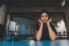 Morenita joven hermosa que presenta al lado de un vintage TV Fotos de archivo