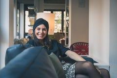 Morenita joven hermosa que presenta en un sofá Fotografía de archivo libre de regalías