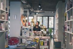 Morenita joven hermosa que presenta en una librería Fotos de archivo