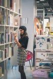 Morenita joven hermosa que presenta en una librería Fotos de archivo libres de regalías