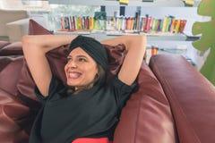 Morenita joven hermosa que presenta en una librería Fotografía de archivo