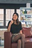 Morenita joven hermosa que presenta en una librería Foto de archivo
