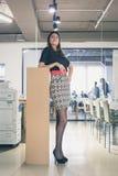 Morenita joven hermosa que presenta en una oficina Fotografía de archivo