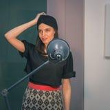 Morenita joven hermosa que presenta en una oficina Imagen de archivo libre de regalías