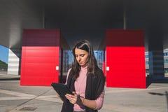 Morenita joven hermosa que trabaja en su tableta Fotos de archivo libres de regalías