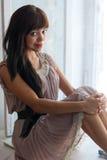 Morenita joven magnífica que se sienta cerca de ventana Foto de archivo libre de regalías