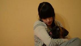 Morenita joven que abraza un perro Primer almacen de metraje de vídeo
