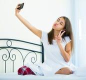 Morenita joven que toma la imagen de ella con smartphone Imagenes de archivo