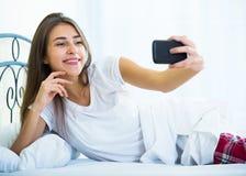 Morenita joven que toma la imagen de ella con smartphone Fotos de archivo libres de regalías