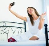 Morenita joven que toma la imagen de ella con smartphone Foto de archivo libre de regalías