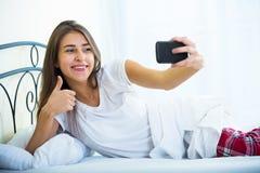 Morenita joven que toma la imagen de ella con smartphone Fotografía de archivo libre de regalías