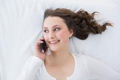 Morenita joven usando el teléfono móvil en cama Fotos de archivo