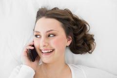 Morenita joven usando el teléfono móvil en cama Imagen de archivo