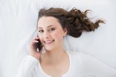 Morenita joven usando el teléfono móvil en cama Imagenes de archivo