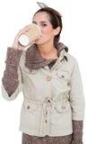 Morenita linda contenta en la moda del invierno que bebe de la taza disponible Fotografía de archivo