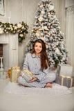 Morenita linda en pijamas debajo del árbol de navidad Fotos de archivo