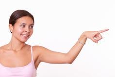 Morenita linda que señala y que mira a su izquierda Fotografía de archivo libre de regalías