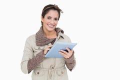Morenita linda sonriente en tableta de la tenencia de la moda del invierno Fotos de archivo libres de regalías