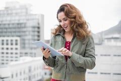 Morenita magnífica feliz en la moda del invierno usando la tableta Fotos de archivo libres de regalías