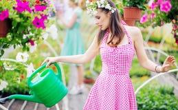 Morenita magnífica que riega las flores imágenes de archivo libres de regalías