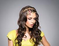 Morenita magnífica, sensual que lleva la corona de lujo de oro sobre fondo gris Fotos de archivo libres de regalías