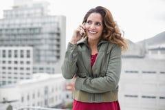 Morenita magnífica alegre en la moda del invierno usando smartphone Imágenes de archivo libres de regalías
