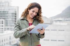 Morenita magnífica sonriente en la moda del invierno usando la tableta Imagen de archivo