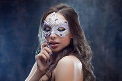 Morenita misteriosa y hermosa con la máscara veneciana Foto de archivo