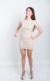 Morenita patilarga joven hermosa en una pequeña altura completa gris del vestido de cóctel de la muchacha risas mismo, emociones  Fotos de archivo