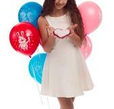 Morenita preciosa de la muchacha con el pelo largo en un vestido blanco con un arco en su cabeza y globos que presentan en un fon Fotos de archivo